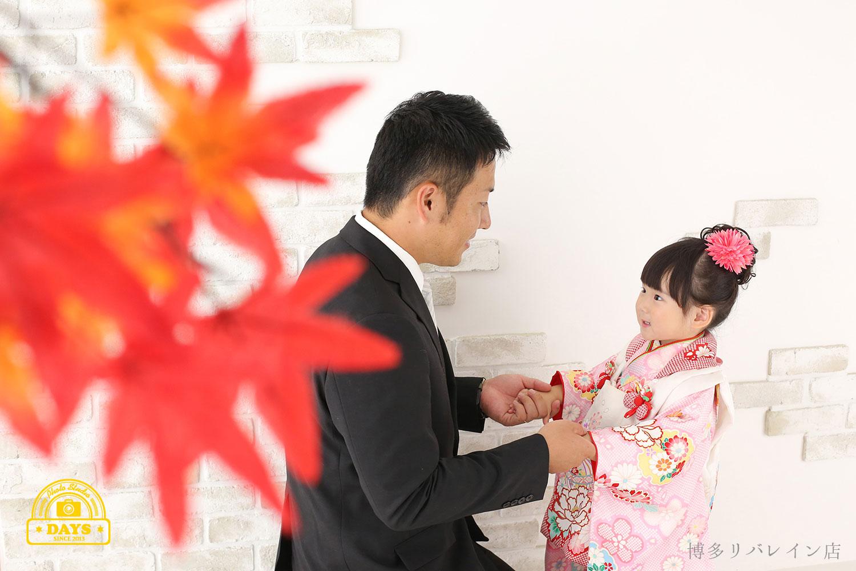 パパと手を取って向き合う七五三の女の子