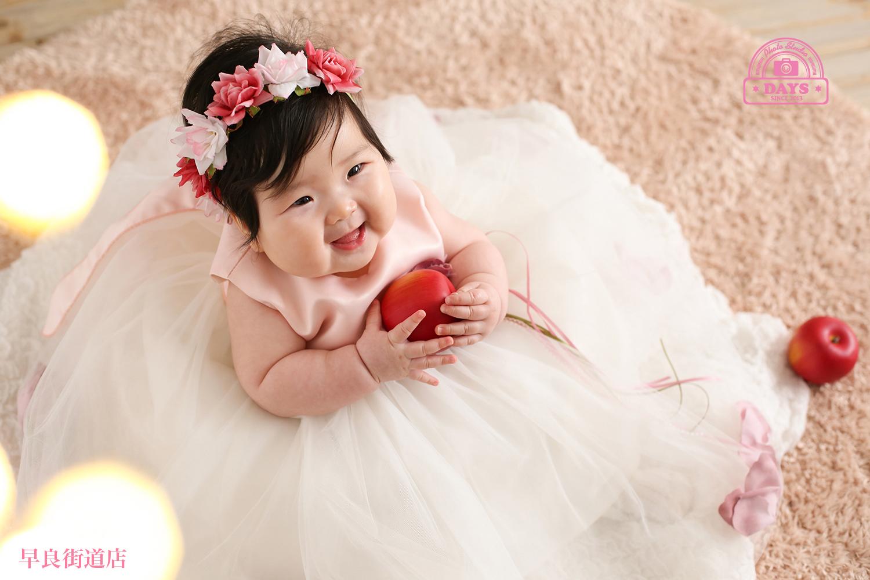 花冠もつけてパパとママに向かってリンゴ持てたよ~と笑いかけるハーフバースデーの女の子の写真