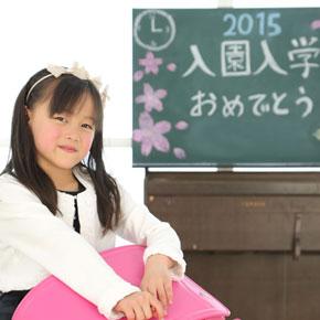 ピンクのランドセルを持っている女の子、黒板に入園入学おめでとう。