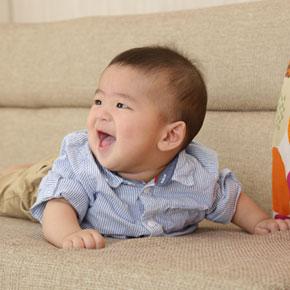 ソファーの上で笑っている赤ちゃん